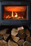 A fireplace or wood stove. In a living room in action, for heating. With firewood Royalty Free Stock Photos