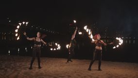Fireshow artists juggling with fire on riverside stock footage