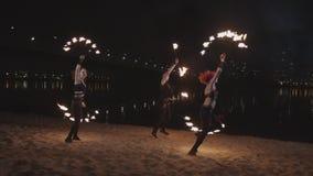 Fireshow-Ausführende, die mit Feuer auf Sand tanzen stock footage