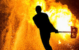 Fireshow performance. Silhouette of man with hammer Royalty Free Stock Photos