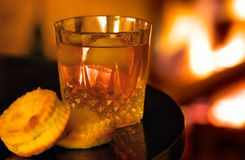Fireside drink with pastries. Backlit by light of a log fire.  Shallow DOF: focus on drink lip Stock Photo