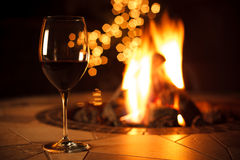 Fireside with a Glass of Wine. A relaxing environment near the fire, enjoying a glass of red wine with some bokeh lights in the background Royalty Free Stock Image