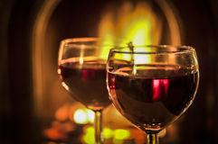 Fireside Wine. Two glasses of red wine beside the fire Royalty Free Stock Photography