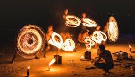 firestarter执行令人惊讶的火展示的小组与闪闪发光在晚上-满月党在泰国夜生活的事件节日 免版税库存照片