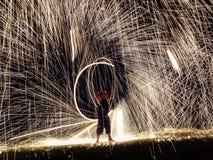 Firestarter que executa a mostra do fogo com os sparkles na noite Fotografia de Stock Royalty Free