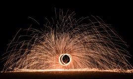 Firestarter que realiza la demostración asombrosa del fuego con las chispas en la noche Imagenes de archivo
