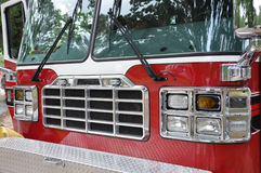 Firetruck. Closeup of the front of a fire truck with trees reflected in the windshield Stock Images