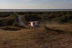Firetruck deploying in the dunes of Schiermonnikoog to fight multiple forest fires. Firetruck deploying in the dunes of the dutch Island Schiermonnikoog to fight stock photo