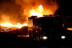 Firetruck and Fire. A firetruck in front of a blazing fire at night Royalty Free Stock Photos