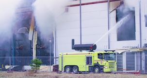 Firetruck que intenta conseguir control sobre un fuego en el edificio industrial almacen de video
