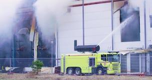 Firetruck que tenta obter o controle sobre um fogo na construção industrial video estoque