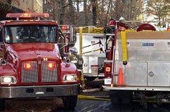 Firetrucks en un fuego de la casa Imágenes de archivo libres de regalías