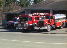 Firetrucks at Station. Firetrucks and vehicles parked in front of station stock image