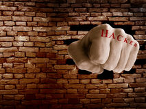 Firewall breach. Hacker fist punching thru a brick wall, online security or firewall concept Royalty Free Stock Photo