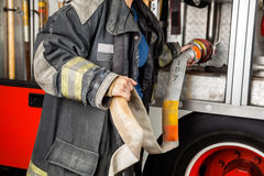 Firewoman Adjusting Hose In Truck Stock Photos