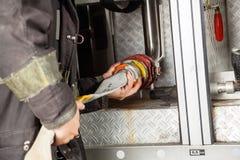 Firewoman ajustant le tuyau dans le Firetruck Image stock