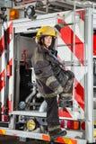 Firewoman anseende på lastbilen på brandstationen Royaltyfria Bilder