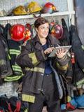 Firewoman que parece ausente mientras que usa la tableta de Digitaces Imagen de archivo libre de regalías