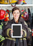 Firewoman Showing Digital Tablet At Fire Station Stock Photo