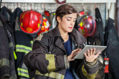 Firewoman Using Digital Tablet At Fire Station Stock Photos