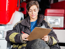 Firewoman Writing On Clipboard Against Trucks Royalty Free Stock Image