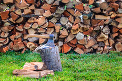 Firewood. An axe in a log in front of stack of firewood Royalty Free Stock Photo