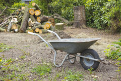 Firewood and barrow. In the garden Stock Photo