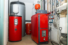 Firewood boiler and puffer thank in the boiler room Stock Photos