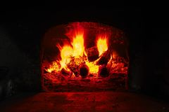 Firewood burning in brick oven, fire flame closeup. Flame on burning wood in stone fireplace from firebricks Royalty Free Stock Photos