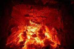 The firewood burning in the fire of the furnace. The wood burning in the fire of the russian furnace. Inside view royalty free stock images