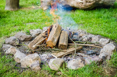 Firewood burning in fire with smoke surrounded by stones Royalty Free Stock Image