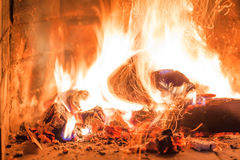Firewood burning in fireplace fire heat red ashes interior Royalty Free Stock Image