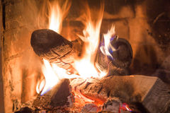 Firewood burning in fireplace fire heat red ashes Royalty Free Stock Images