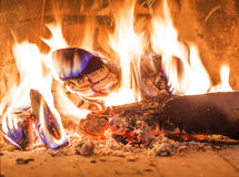 Firewood burning in fireplace fire red ashes heat Royalty Free Stock Image