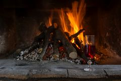 The firewood burning in fireplace and a glass of wine. Burning fireplace in the winter season. The firewood burning in fireplace and a glass of wine close-up royalty free stock photo