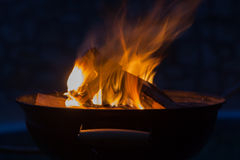 Firewood burning in grill bowl Stock Photography