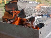Firewood burning in metal tray close-up. Firewood burning in a rusty metal tray for broiling pan in a fine sunny weather, close-up Stock Image
