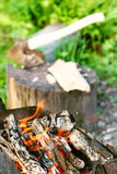 Firewood burning in outdoor brazier close up. With ax in stump on background Stock Images