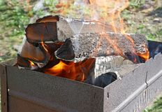 Firewood burns in rusty metal tray Royalty Free Stock Photos