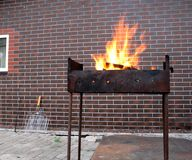 Firewood and fire in the old rusty charcoal grill. On brick wall background Stock Photos