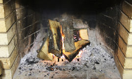 Firewood in the fireplace burning in wintertime Royalty Free Stock Photos