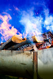 Firewood in grill. Burning firewood in a grill outdoor which becomes hot charcoal for barbecue royalty free stock images