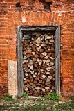 Firewood lies in the doorway, red brick wall. The firewood lies in the doorway on the threshold, a red brick wall Stock Image