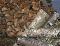 Firewood and Logs. Stacked firewood with a pile of logs ready to be sawed Royalty Free Stock Images