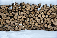 Firewood logs in snow. Firewood put in a woodpile brought by snow. Winter in the village Royalty Free Stock Images