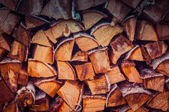 Firewood logs stacked in piles. Red tone. Stock Photos