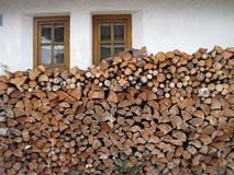 Firewood is lying under the windows Royalty Free Stock Photos