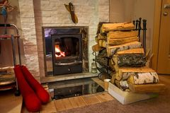 Firewood near burning fireplace. Red felt boots stand. accessories stand marble near house wall. Firewood near burning fireplace. Red felt boots stand stock images
