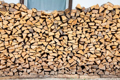 Firewood pile along a wall. Stack of firewood logs wood, for fire along a house wall, almost covering a window Royalty Free Stock Photos