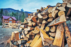 Firewood pile near wooden house. Nature fuel Stock Photo